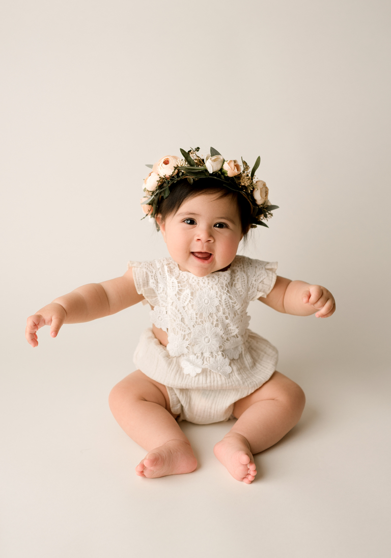 asian baby sitting in photography studio with a flower crown