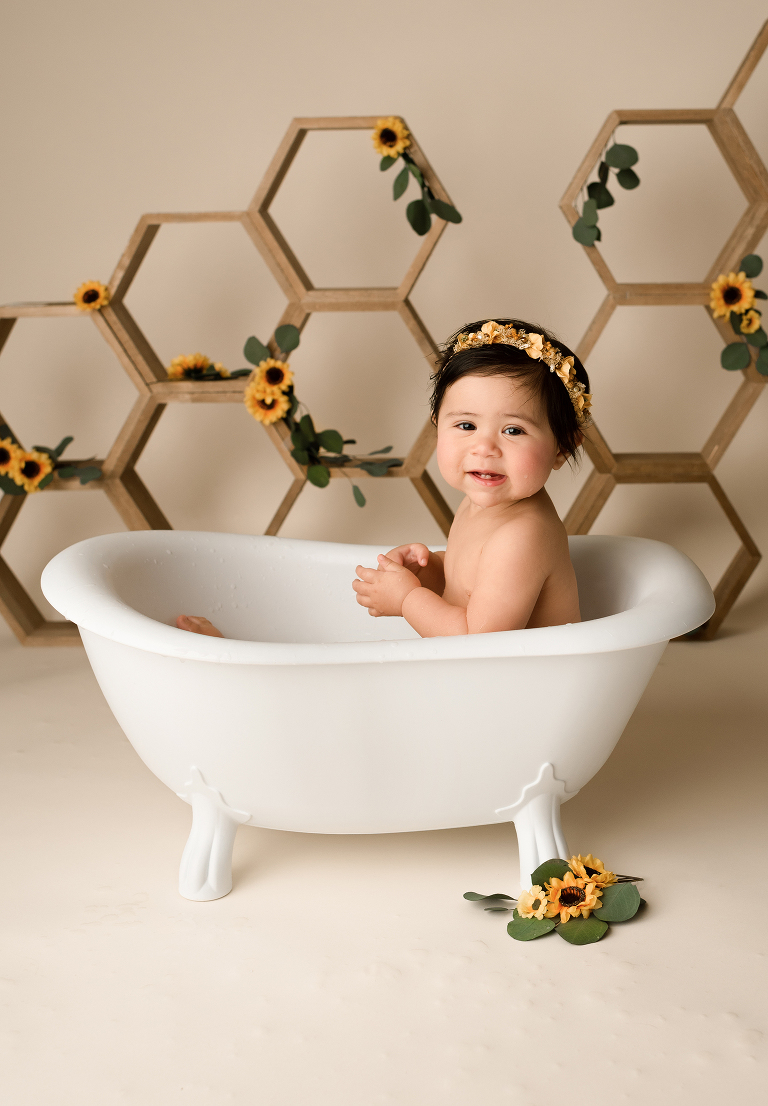 Baby in white bathtub during cake smash photoshoot