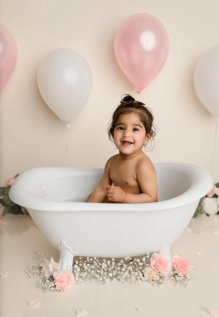 Baby sitting in a miniature bathtub